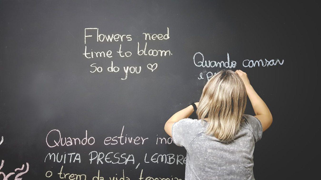 Osoba pisząca na tablicy w wielu językach
