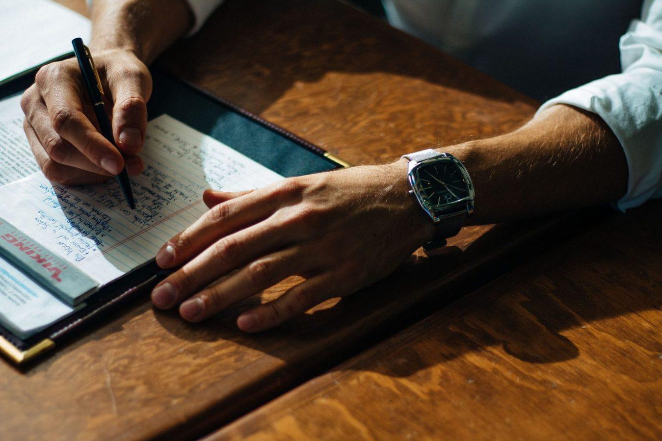 Człowiek piszący na papierze z bliskiej odległości