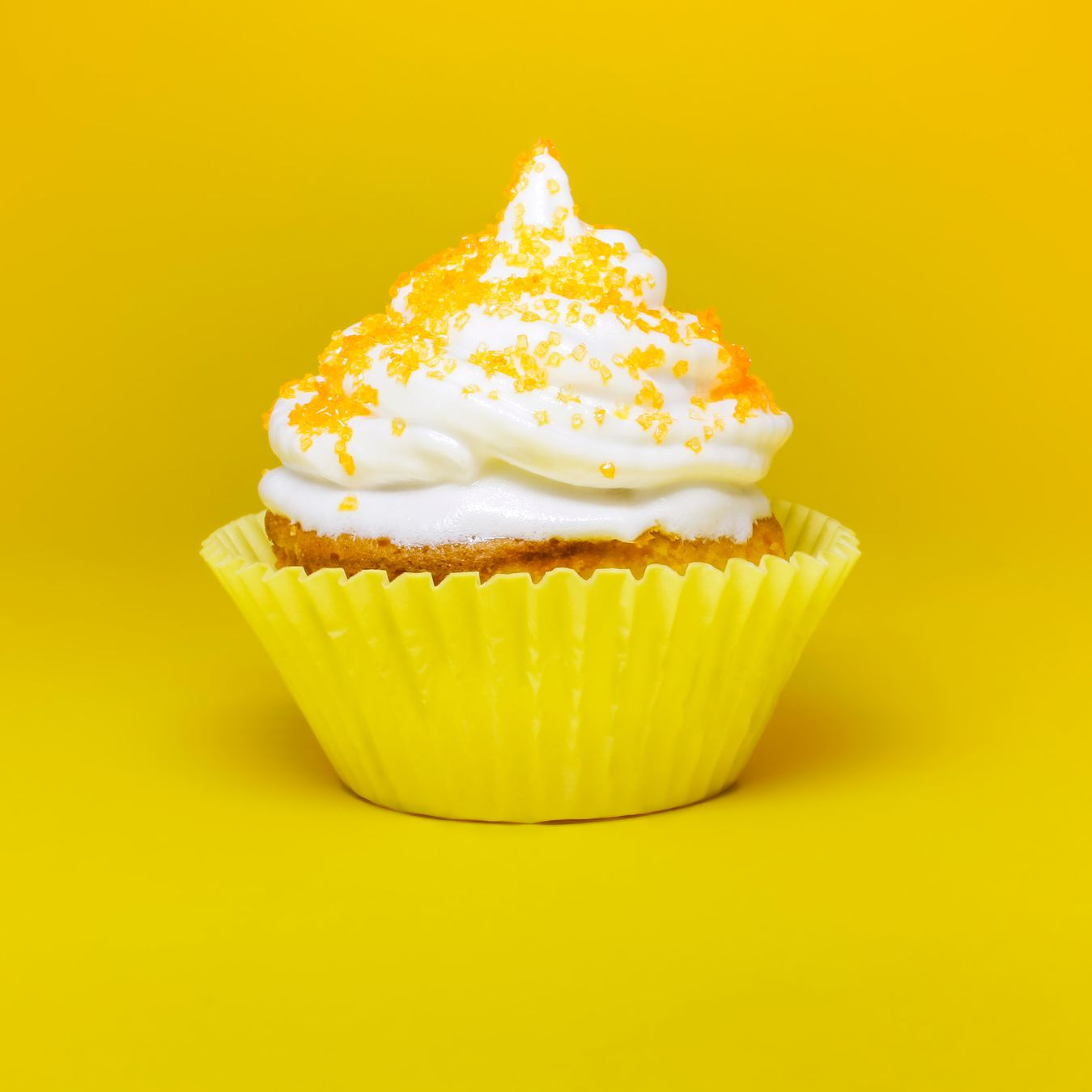 Cupcake with white topping and yellow sprinkles.
