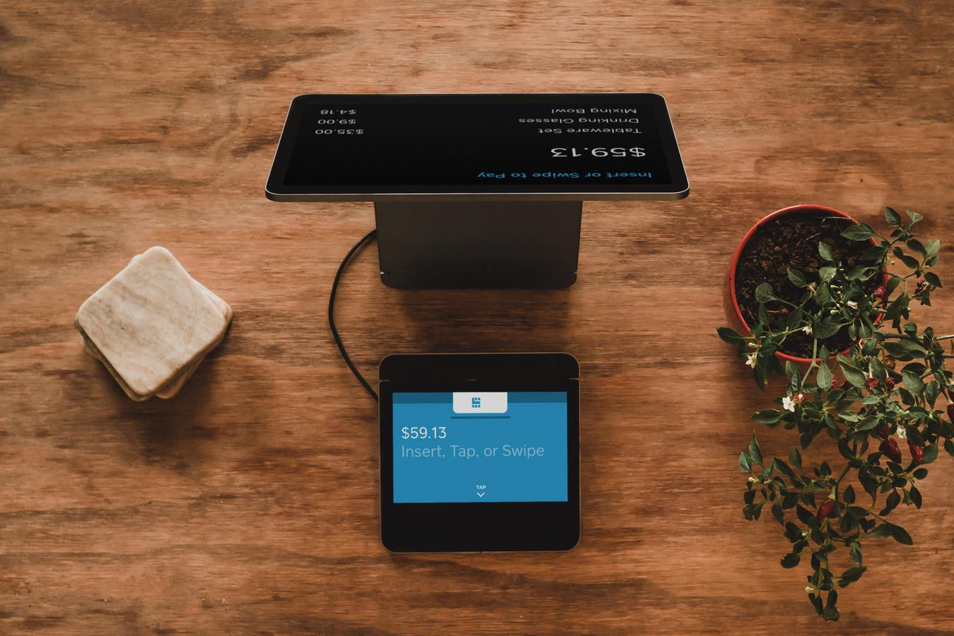 payment pad and tablet on a wooden desk