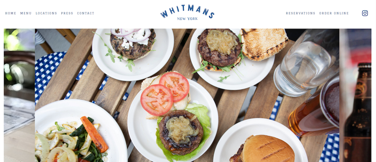 The whitmans restaurant website located in New York, showing open faced hamburgers