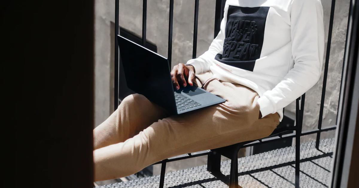 Man Sitting and Browsing on Laptop
