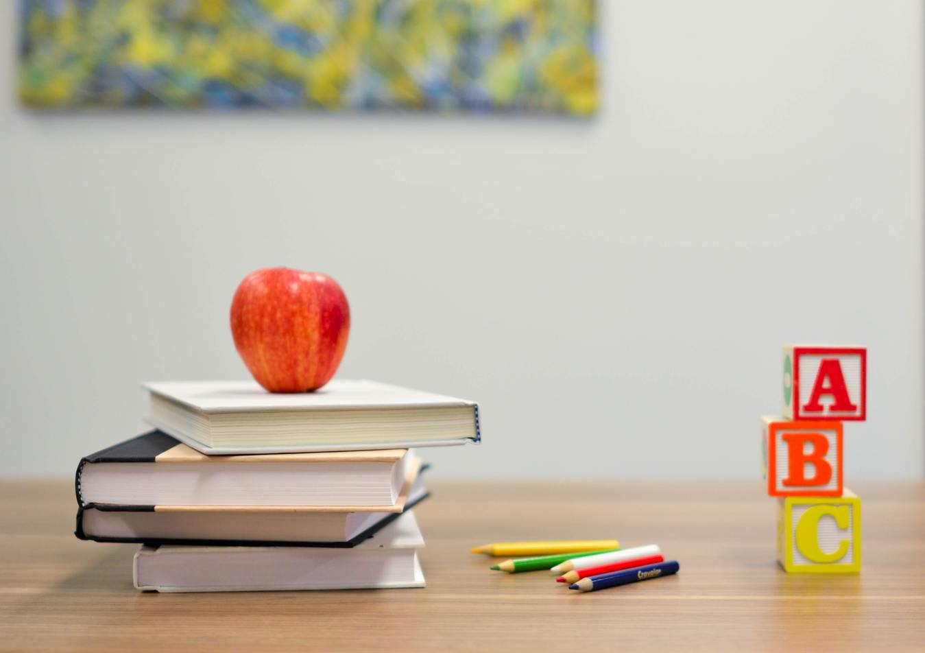 Books, pens, an apple and abc blocks on a table
