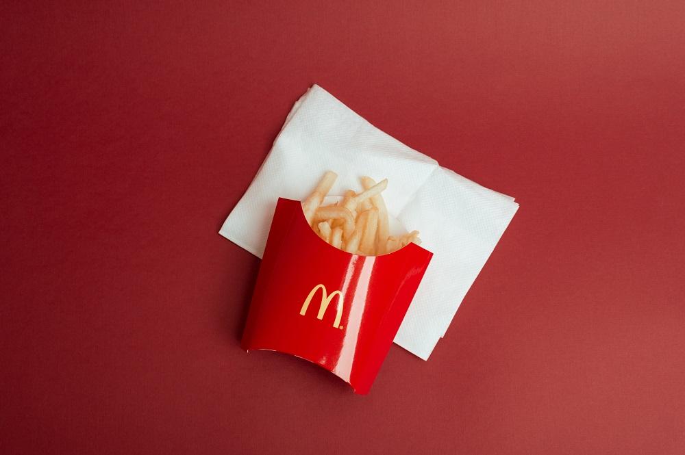 Pommes in McDonalds Verpackung auf rotem Tisch