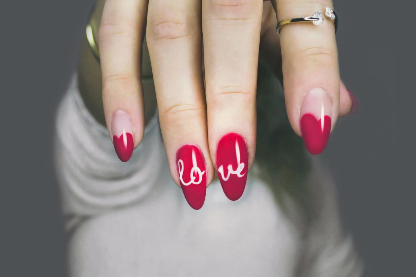 Paznokcie pomalowane na czerwono, z napisem Love
