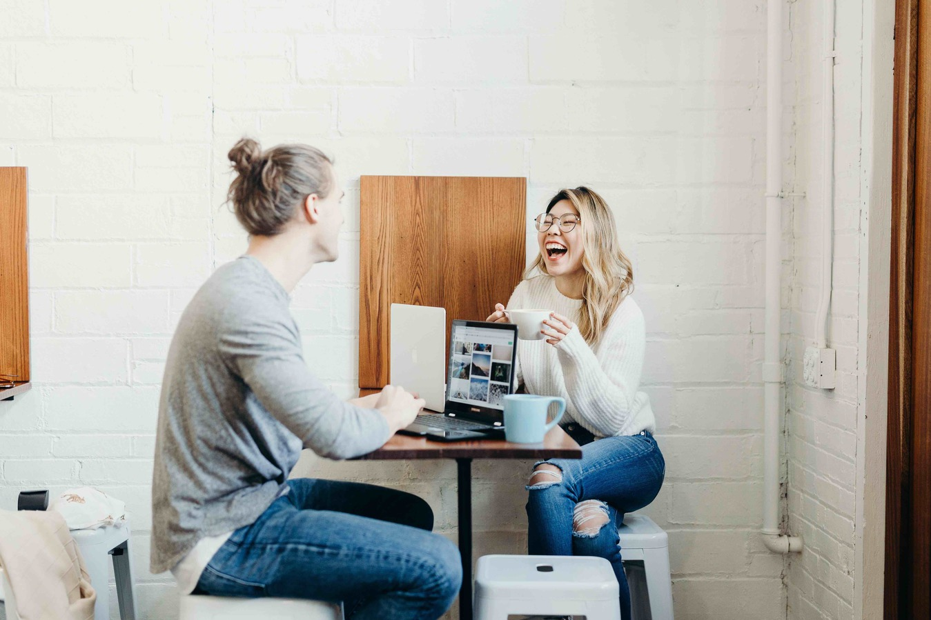 Man and Woman Sitting Laughing in an Office Environment