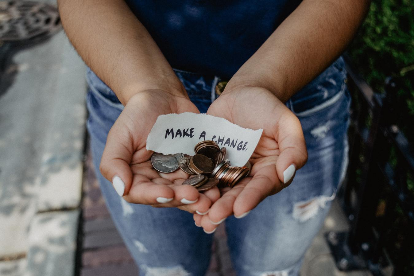 Person donating coins with a note