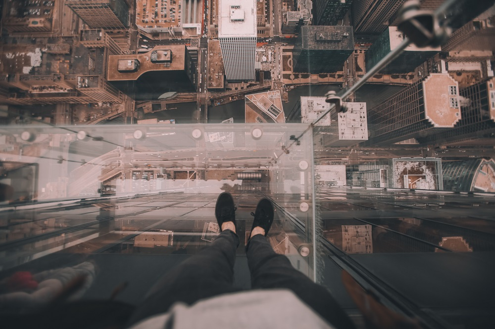 Person looking down through glass floor in skyscraper to streets below