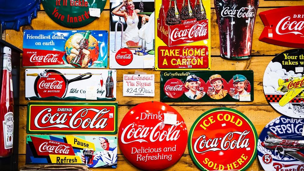 Auswahl an alter Coca-Cola-Werbung an Holzwand genagelt