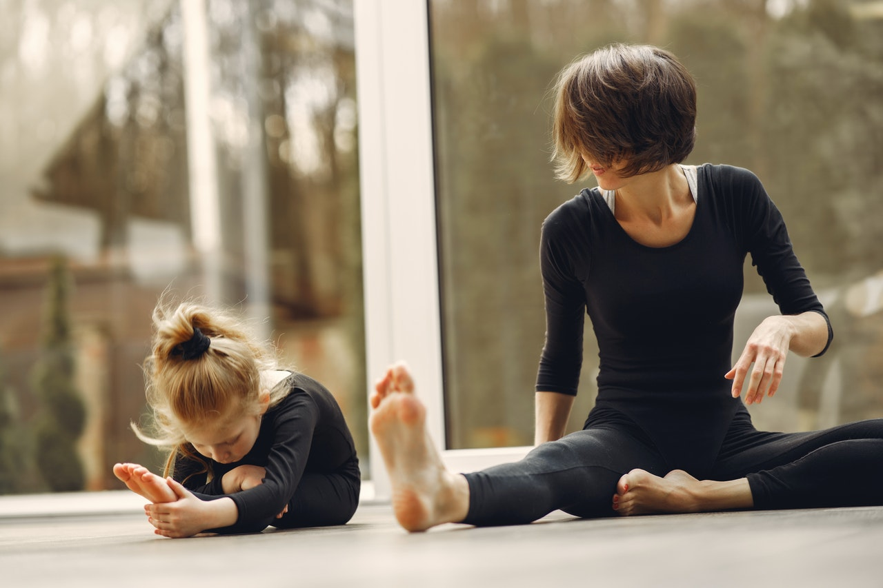 Unrecognizable Female trainer teaching girl doing forward fold yoga