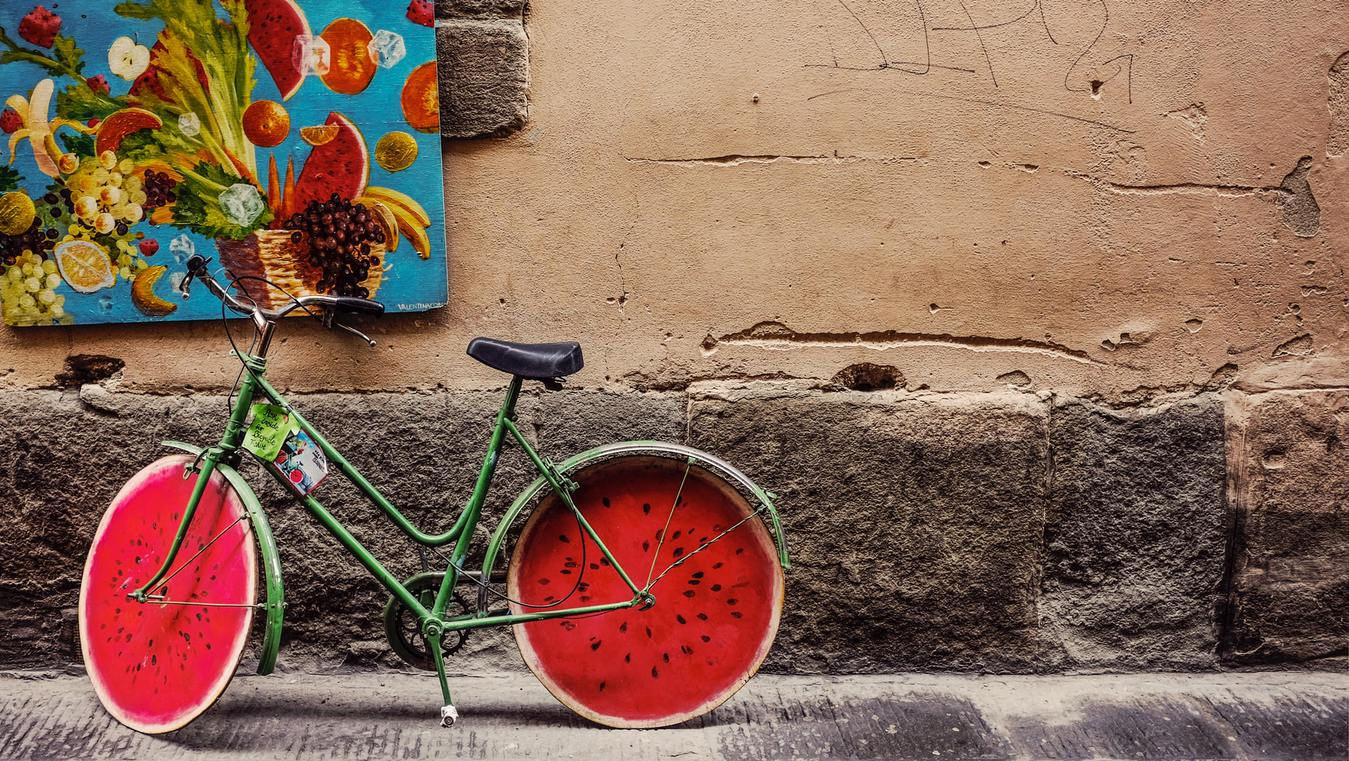 Bicycle painted like a watermelon parked on street