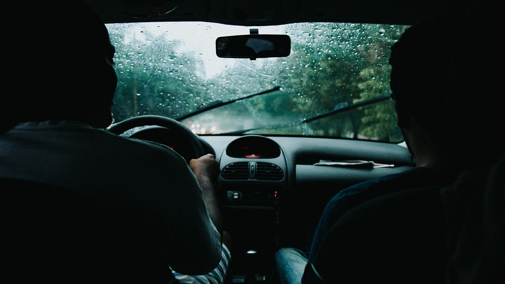 Visão do para-brisa de duas pessoas dentro de um carro em movimento