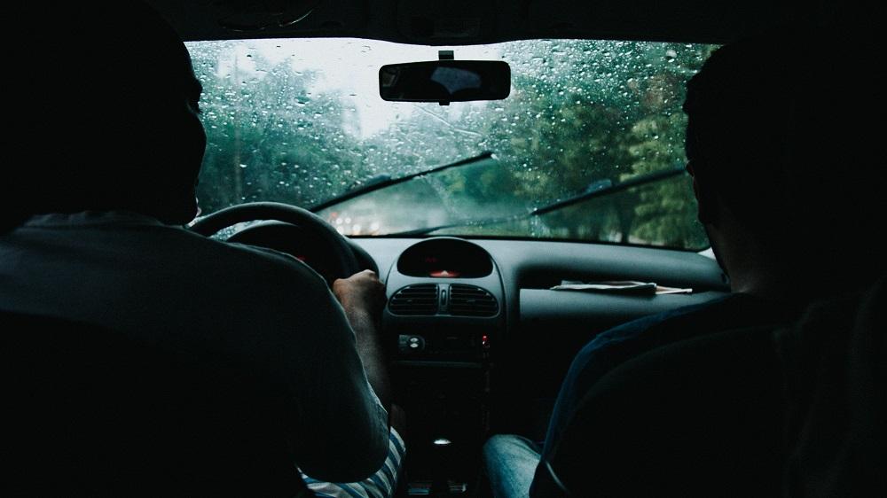 Vista de duas pessoas dentro de um carro em movimento