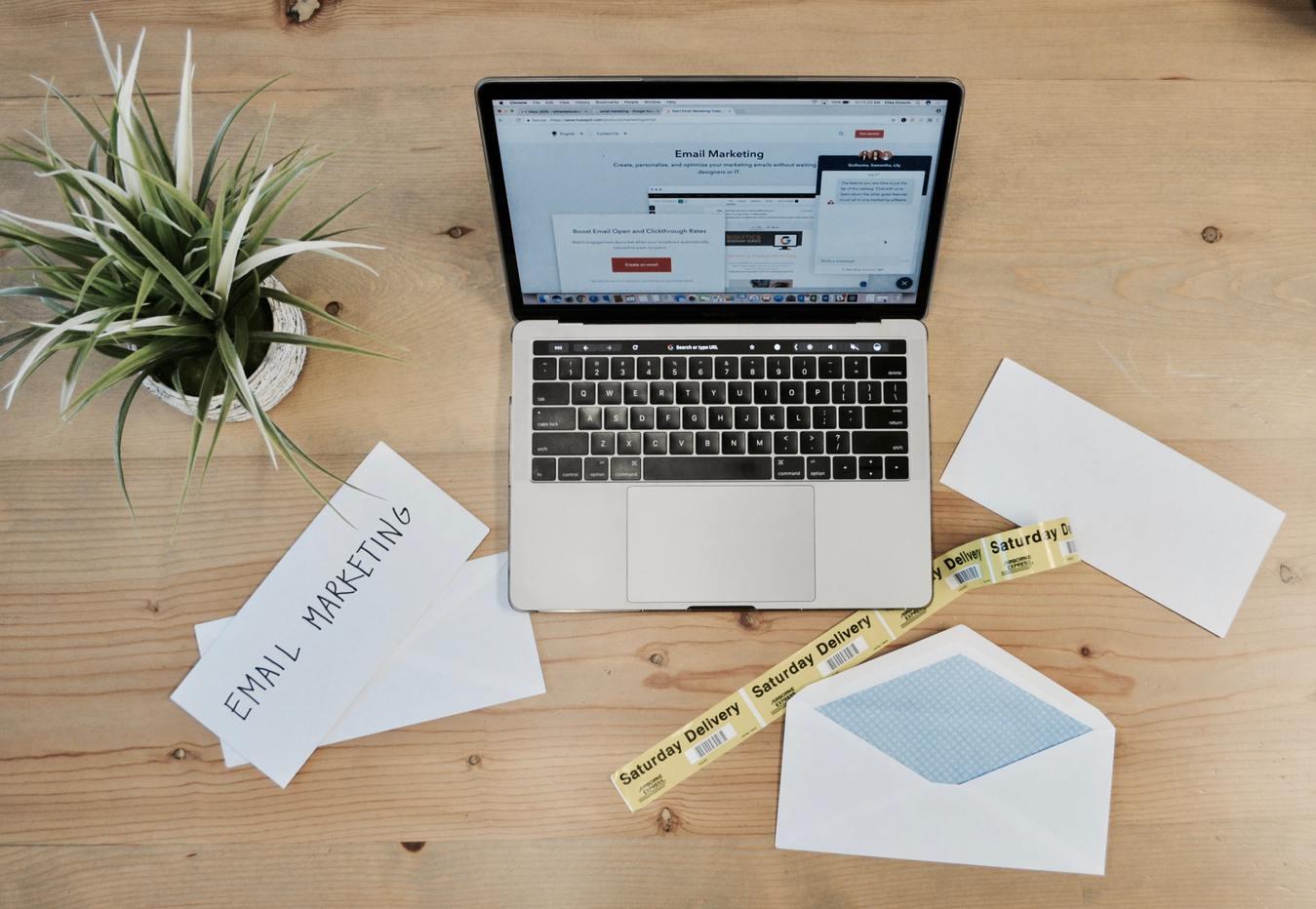 Email marketing portátil sobre uma mesa com papéis e uma planta