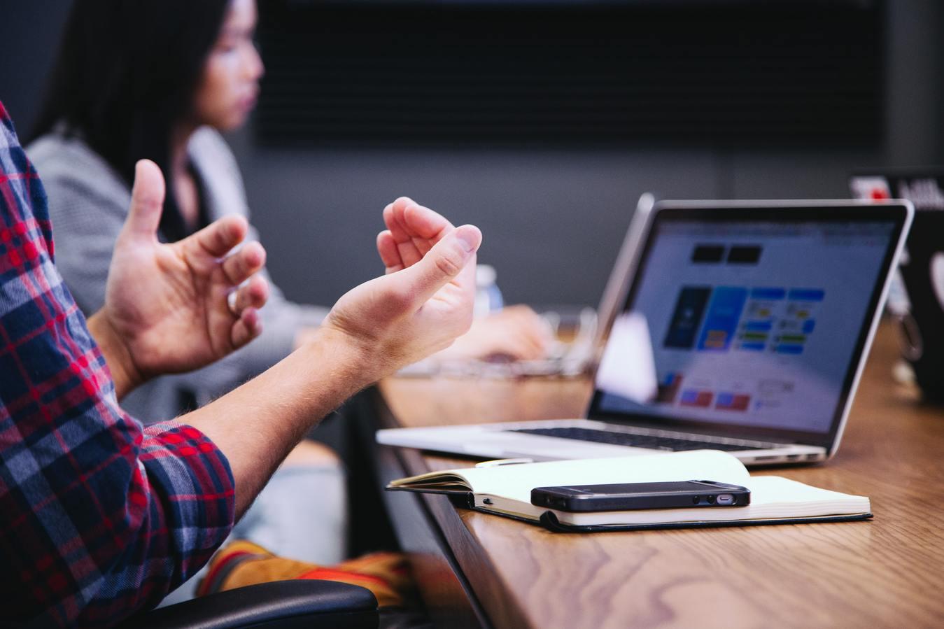 Uma equipa a falar numa sala de conferências com um portátil e um caderno sobre a mesa