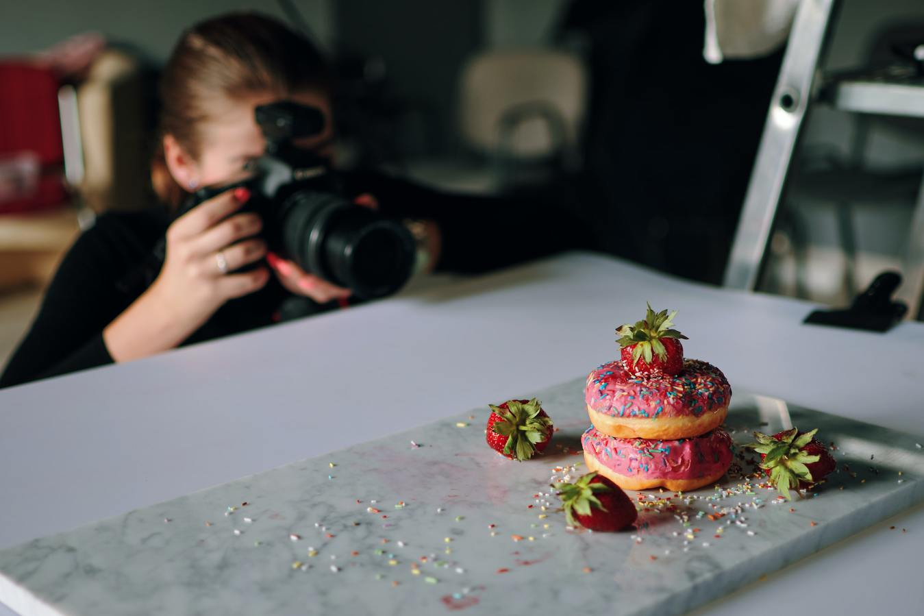 Girl taking a photo of cakes inside