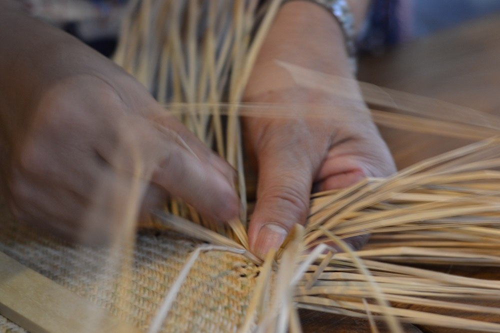 close up of hands weaving basket