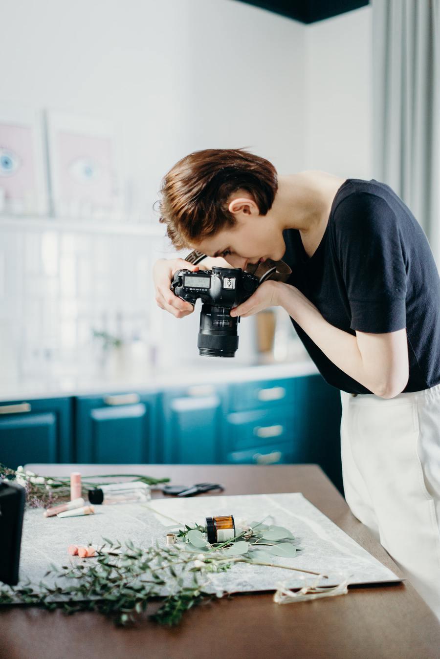 Kobieta w czarnej koszuli robiąca zdjęcia produktów w aranżacji z roślinami – z góry