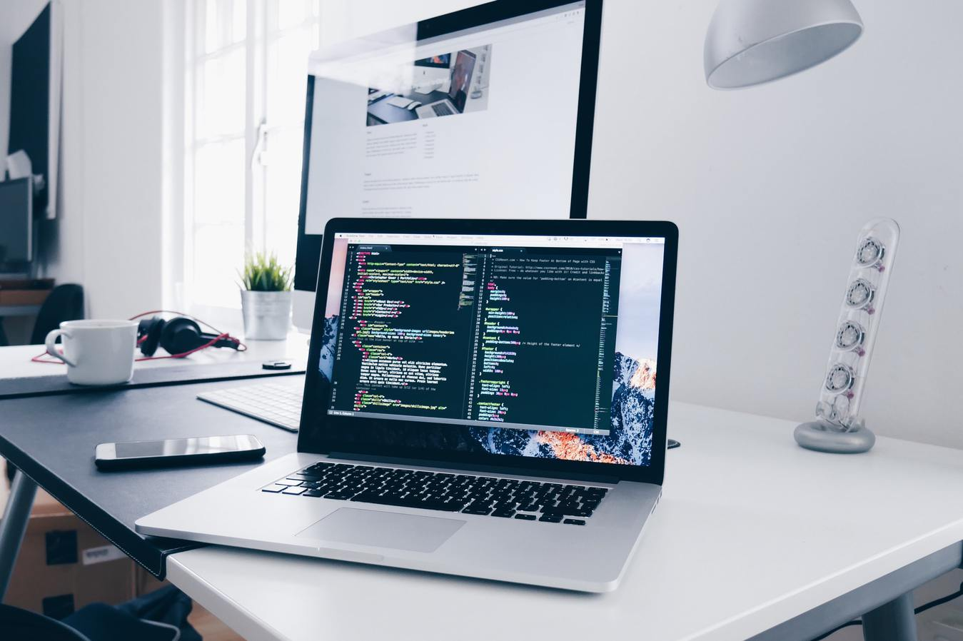 Laptop z kodem na ekranie, na białym biurku.