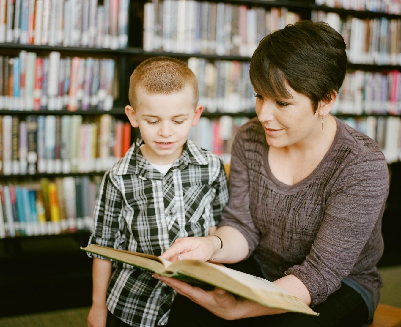 Kobieta z książką w ręku ucząca małe dziecko.