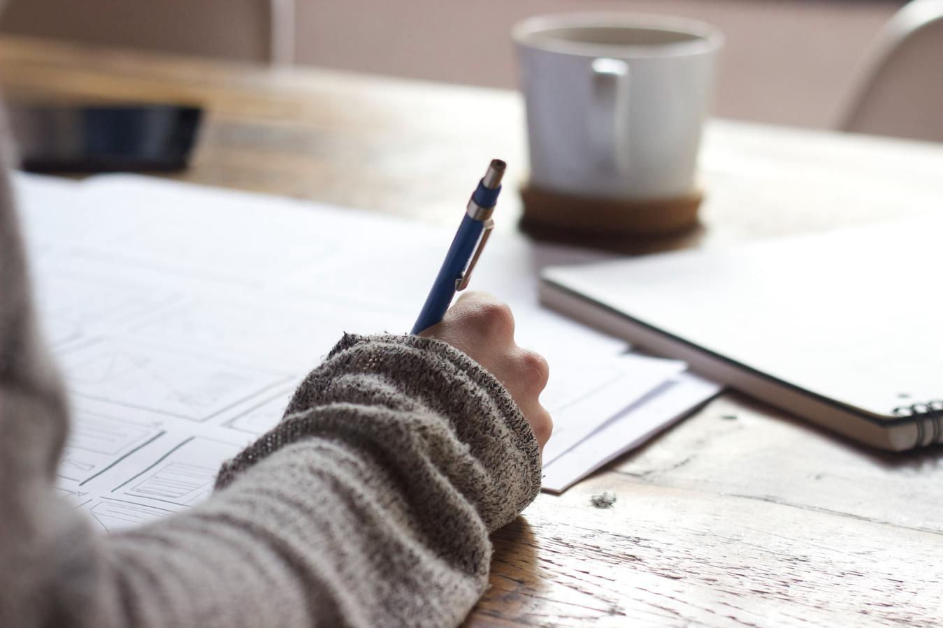Osoba pisząca w notesie,  kubek kawy na stole