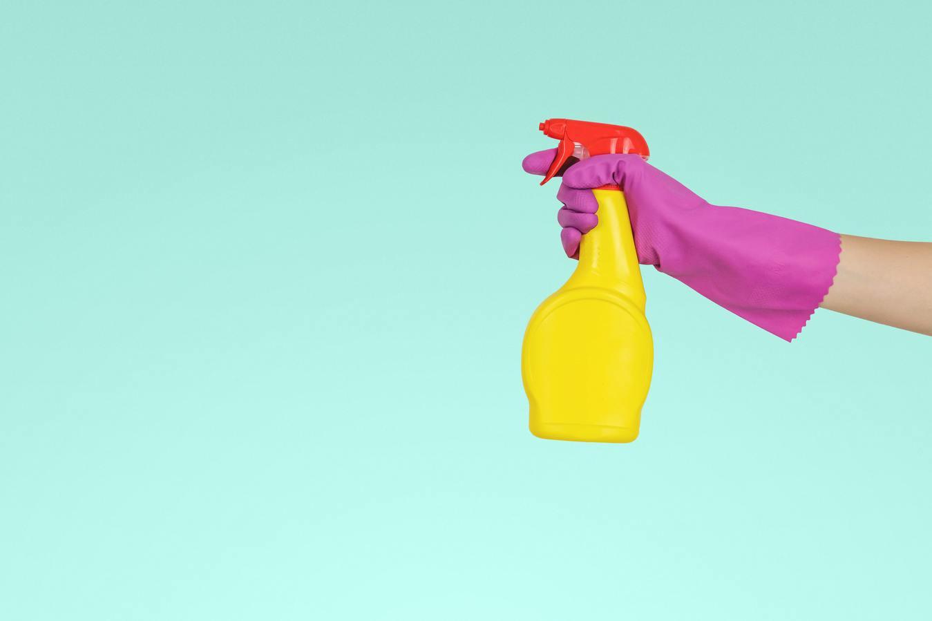 Una persona sosteniendo una botella de spray amarilla con fondo azul