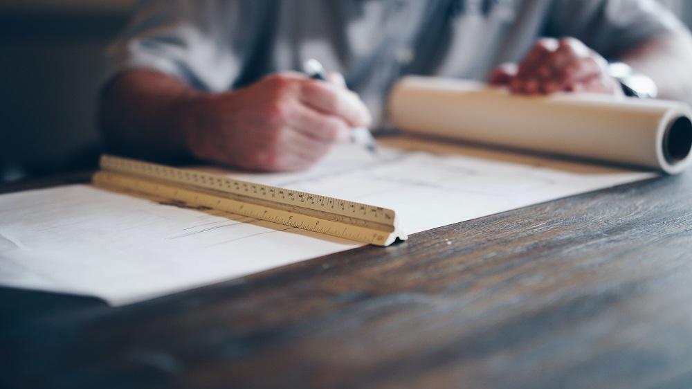 Pessoa desenhando uma blueprint num papel