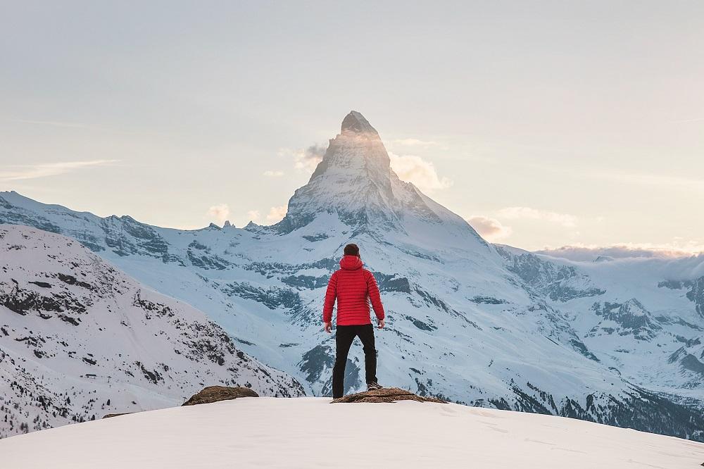 Pessoa no topo de uma montanha a olhar para o pico