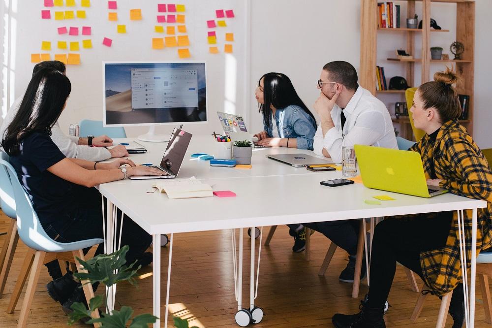 Sala de reuniões com pessoas olhando para uma tela
