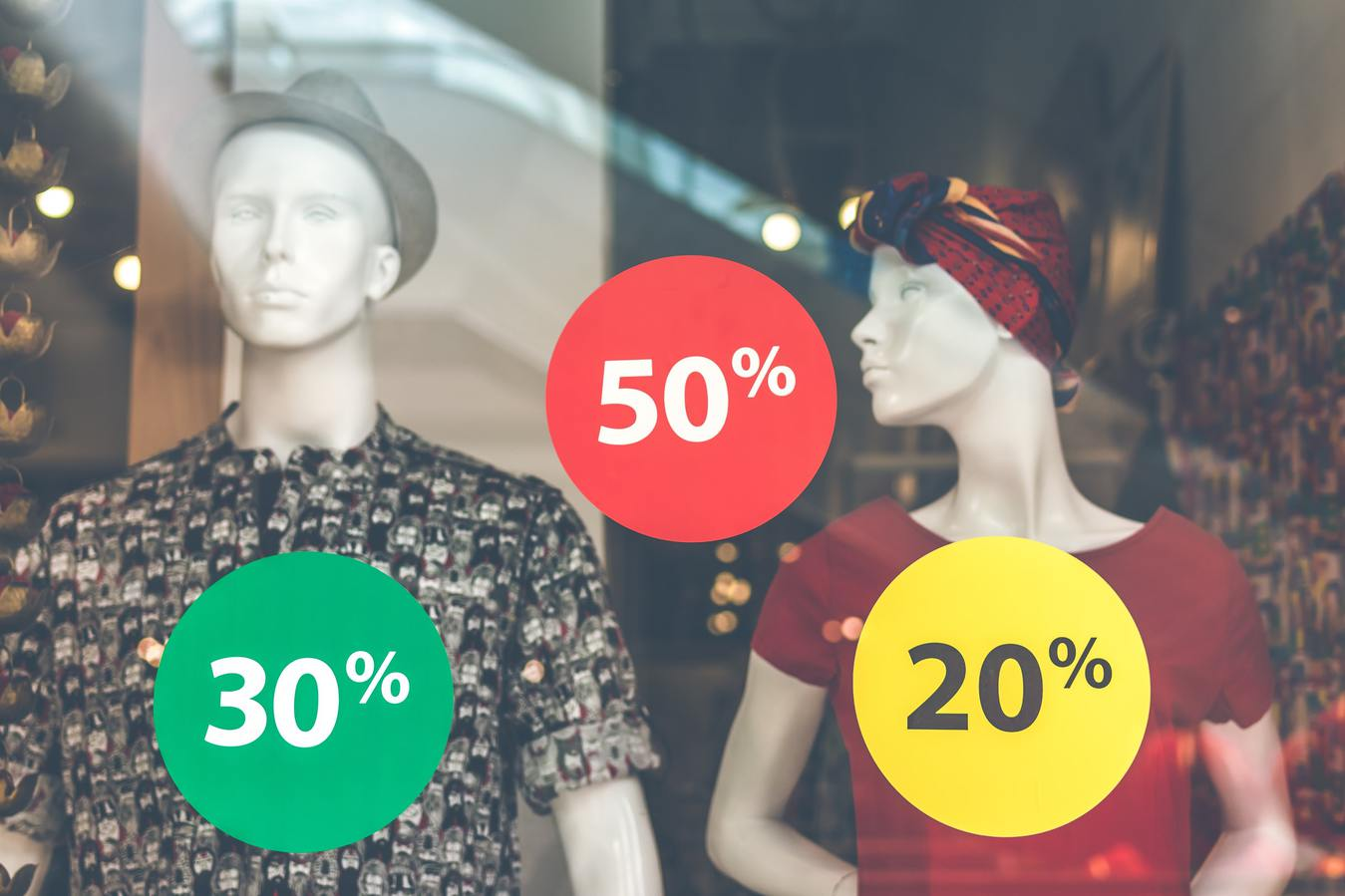 Shop window with sale stickers and mannequins