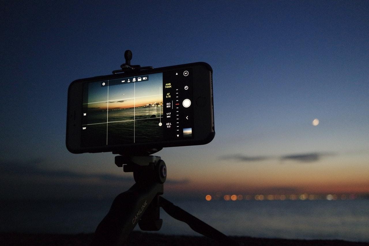 Smartphone tomando fotos en trípode por la noche