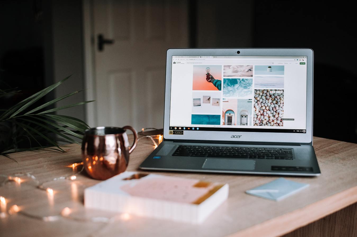 Strona internetowa wyświetlająca się na laptopie, stojącym na biurku, na którym leżą lampki.