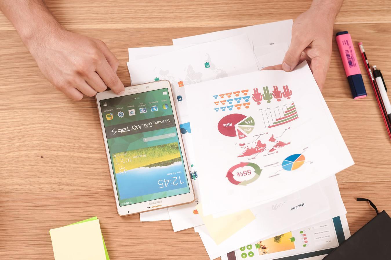 Trabalhando em casa com papeis, com gráficos e tablet em uma mesa