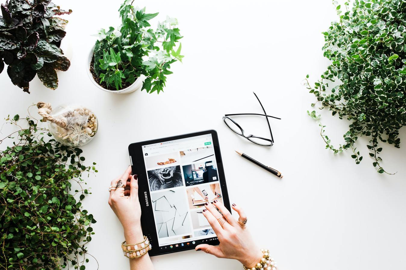orang membuka toko online di tablet di antara tanaman