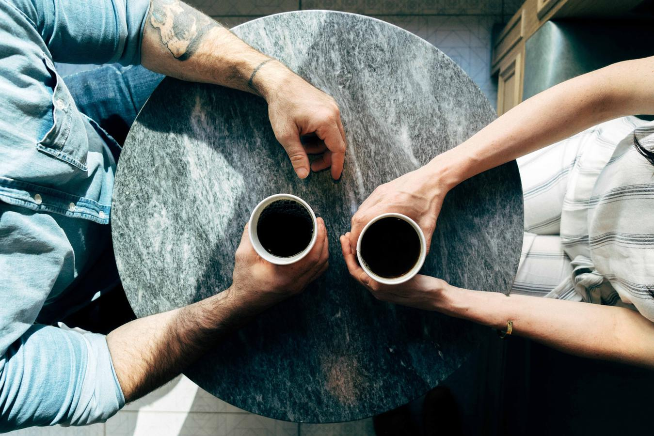 Two people drinking coffee top view of table and arms