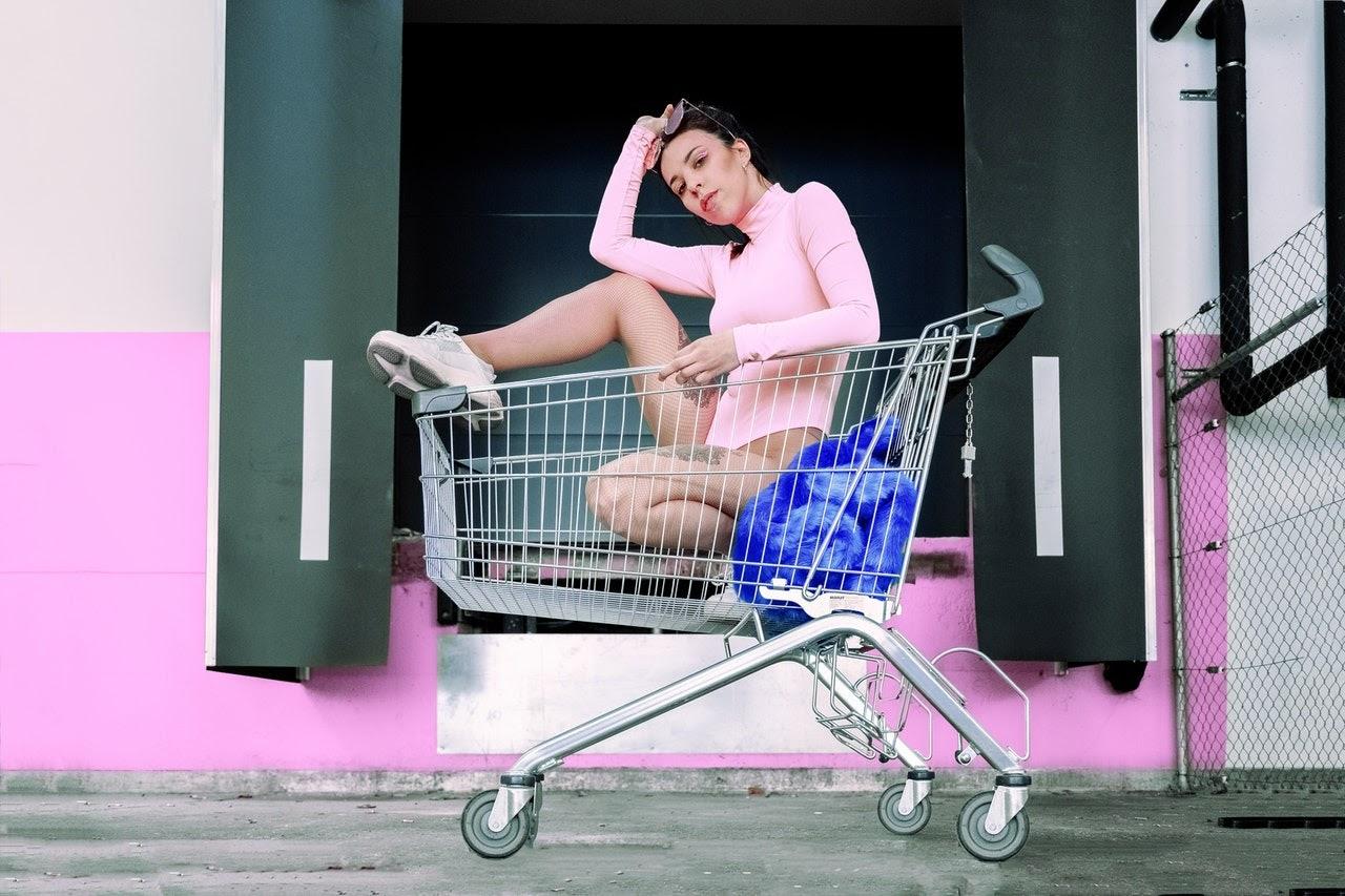 Foto einer Frau im rosa Bodysuit posiert in Einkaufswagen