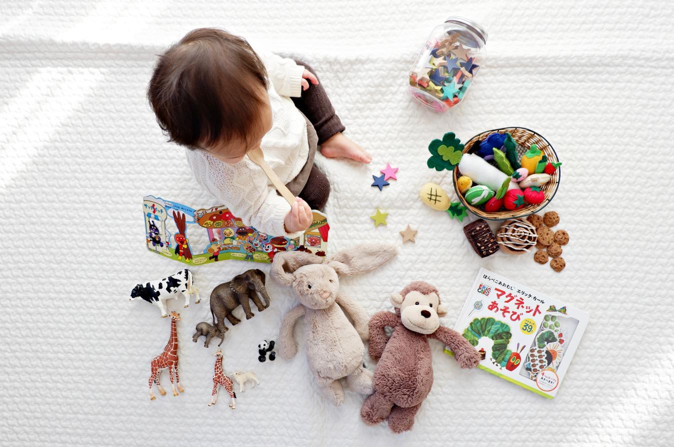 Een kind zit op een witte deken met speelgoed