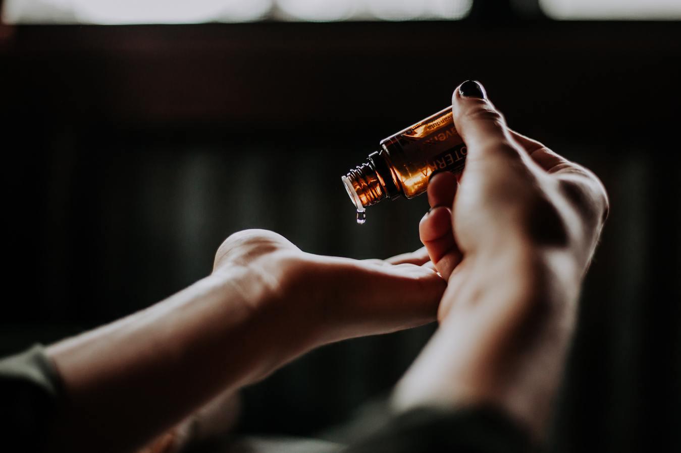 Flasche mit Lotion, die auf eine Hand gegossen wird