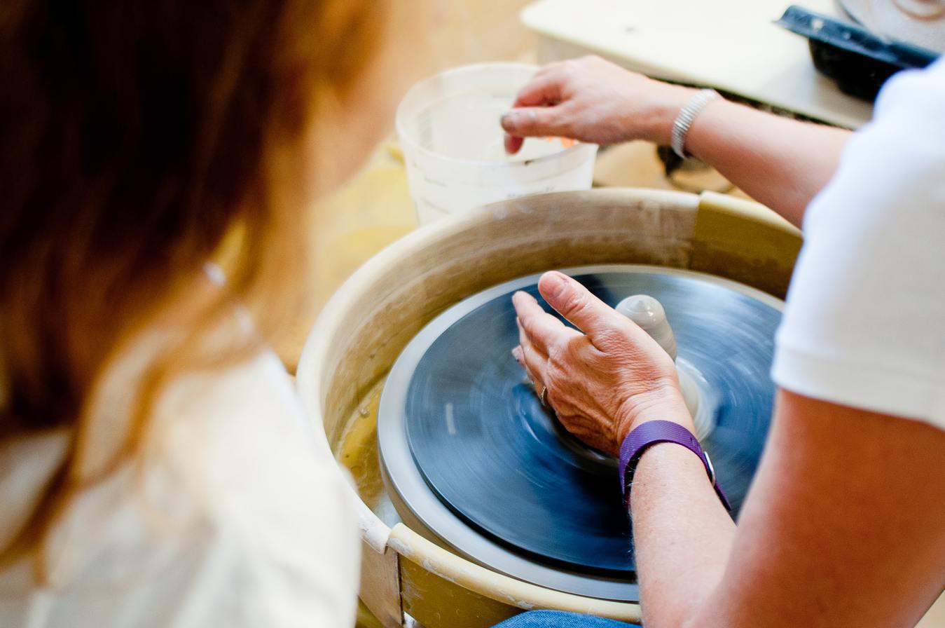 Persoon die een pot van klei op een draaitafel maakt