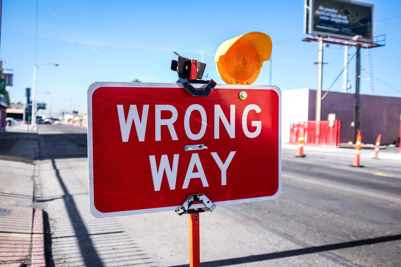 Verkeerdbord verkeerde kant naast een weg met blauwe lucht
