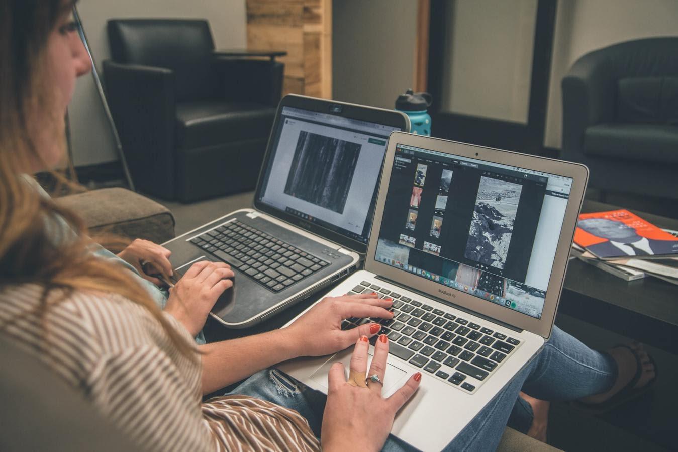 Zwei Leute sitzen und arbeiten an Laptops