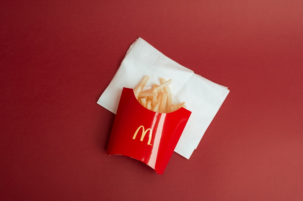 batatas fritas na embalagem do McDonald's sobre uma mesa vermelha