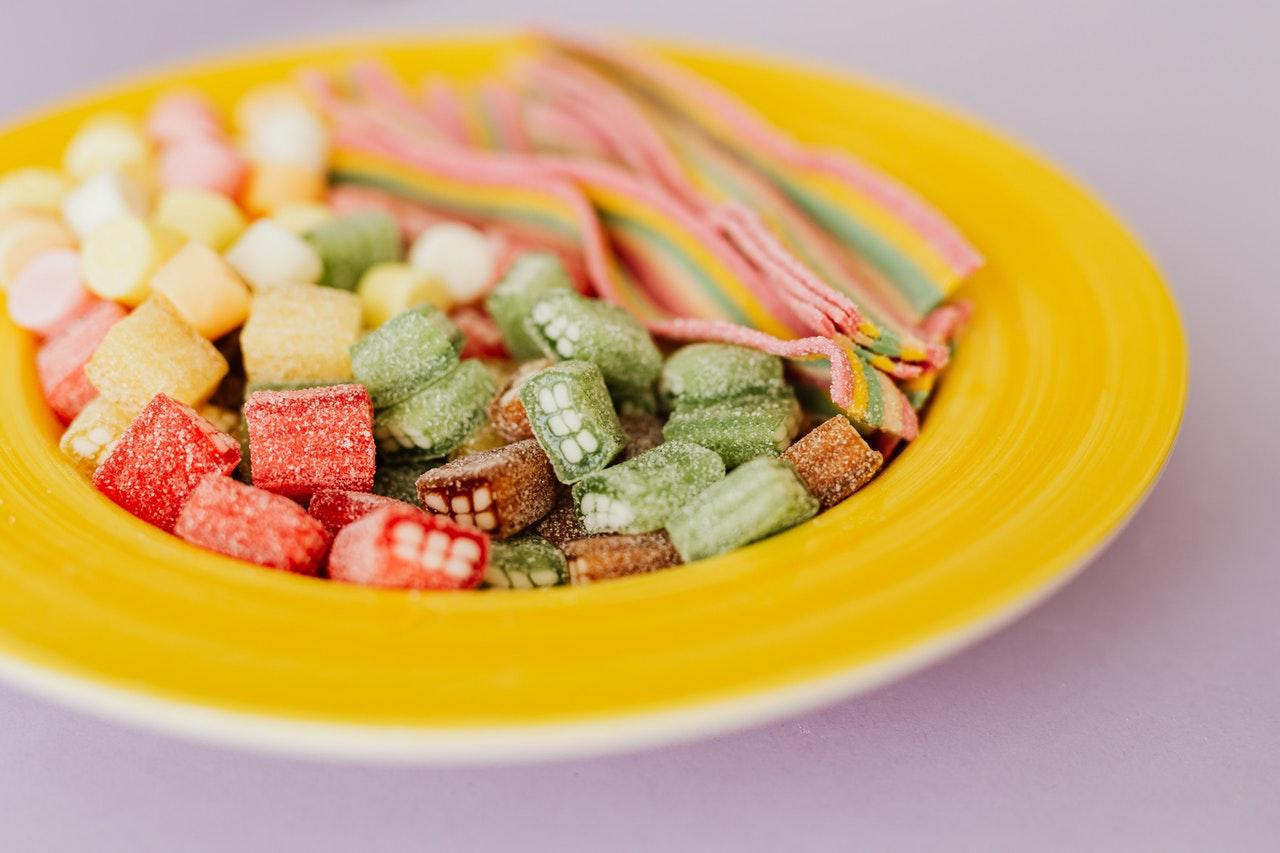 Des bonbons gommeux multicolores  dans un plat jaune avec un arrière plan blanc