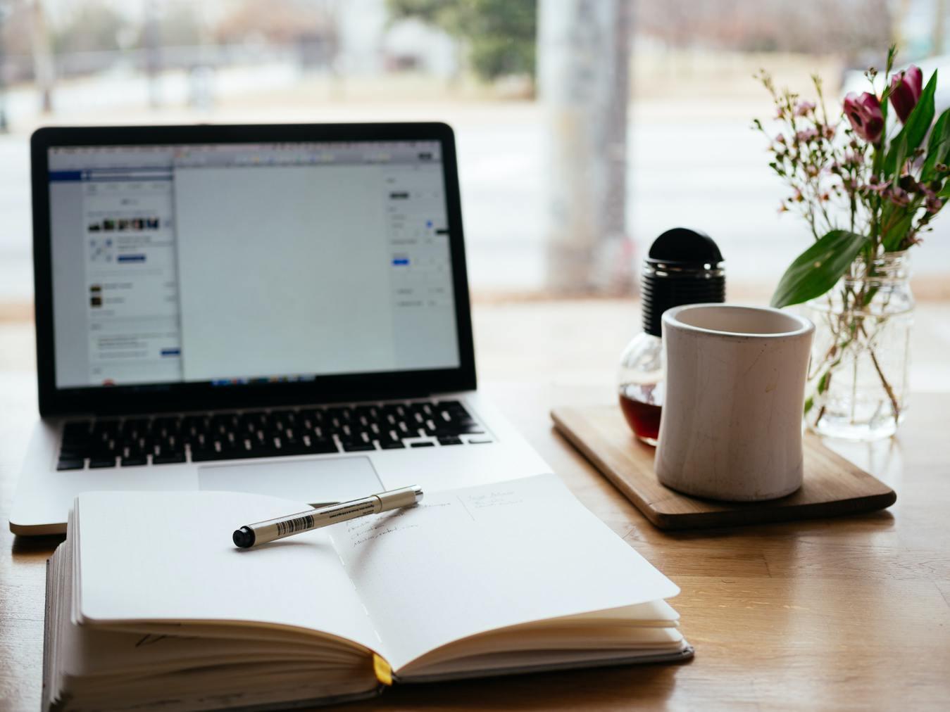 Caderno aberto sobre a mesa ao lado uma caneca e um notebook