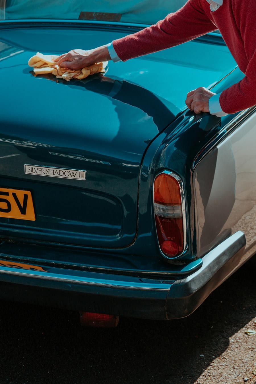 Una persona encerando un auto