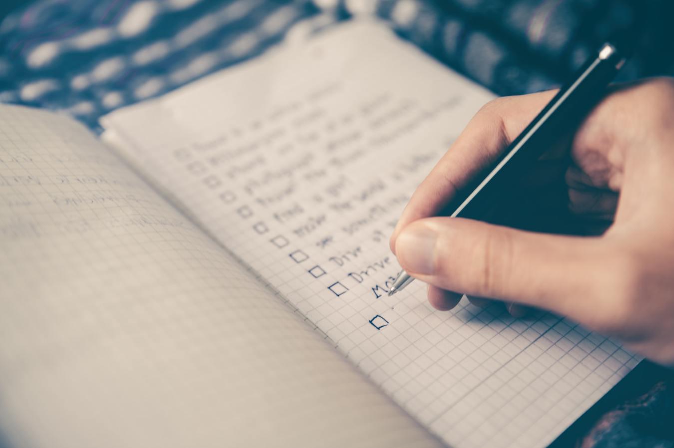 Een persoon die een checklist in een notitieboek schrijft