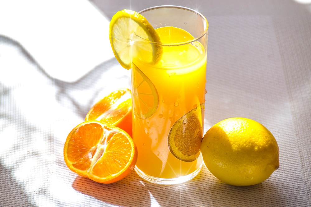 copo de suco de laranja ao lado de um limão e uma laranja cortada