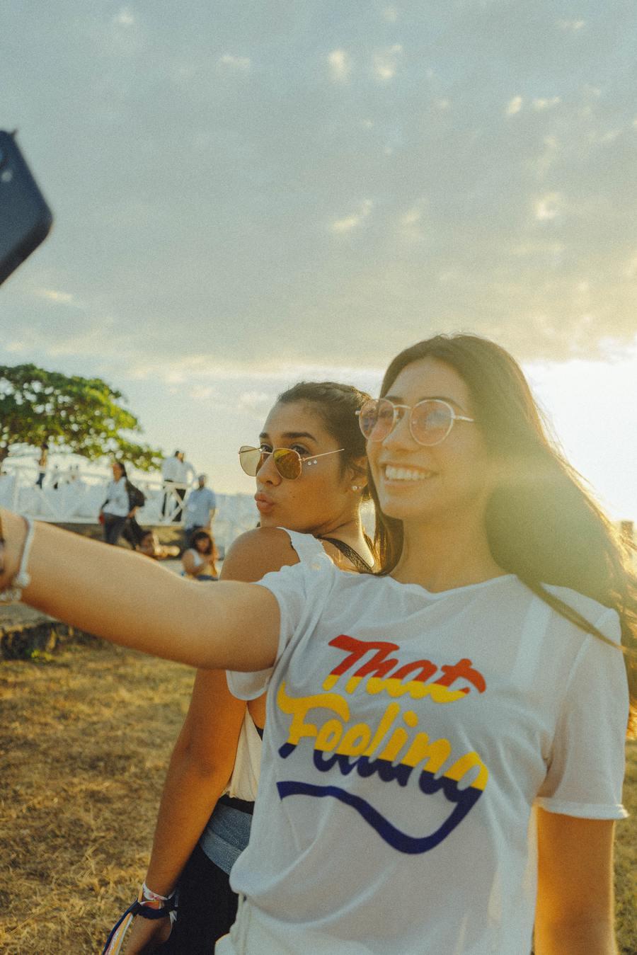 Duas moças tirando selfie na praça