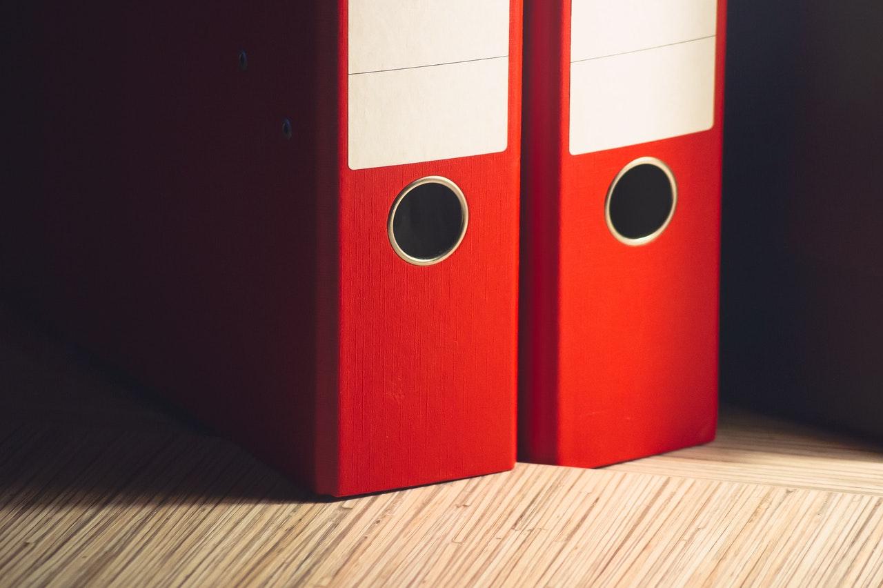Due raccoglitori rossi sulla mensola con file aziendali