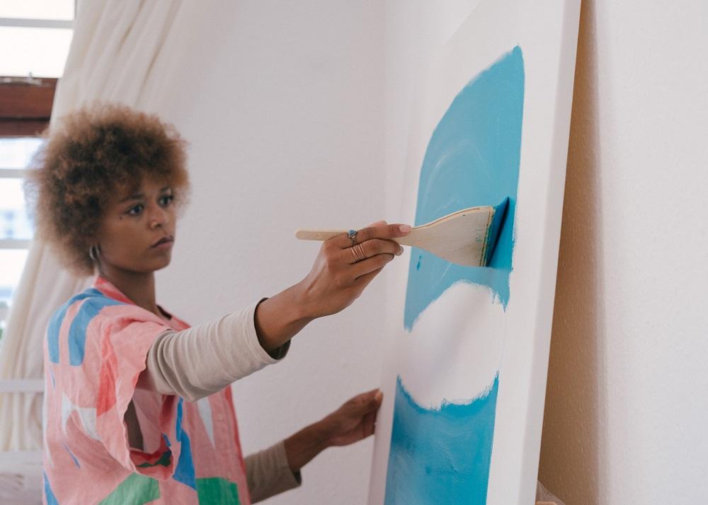 Une femme qui peint en bleu sur un tableau
